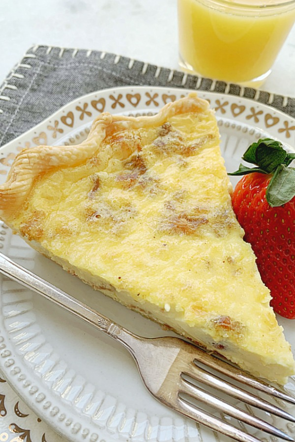 slice of quiche lorraine on plate with strawberry