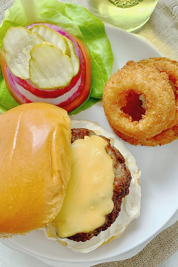 overhead view of burgers on plate with toppings and onion rings