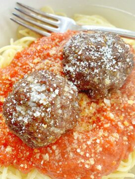 two air fryer meatballs on top of spaghetti and sauce