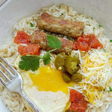 breakfast rice bowl overhead view with orange juice and a fork