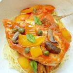 chicken cacciatore in a dish over pasta