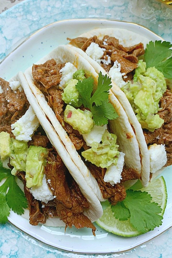 three steak tacos on a plate
