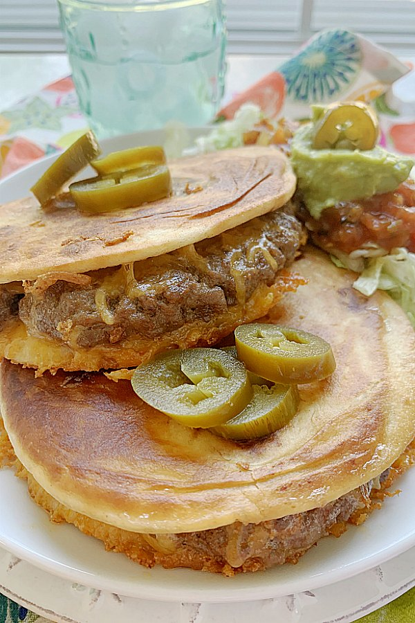 close of quesadilla burger topped with jalapeño peppers