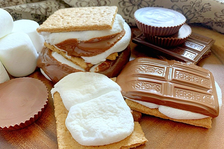 horizontal crop of air fryer s'mores on a platter with stacked chocolate bars, reeses cups and marshmallows