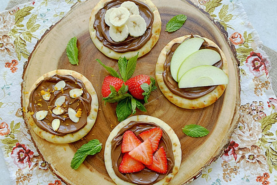 wooden charger topped with four different nutella pizzas