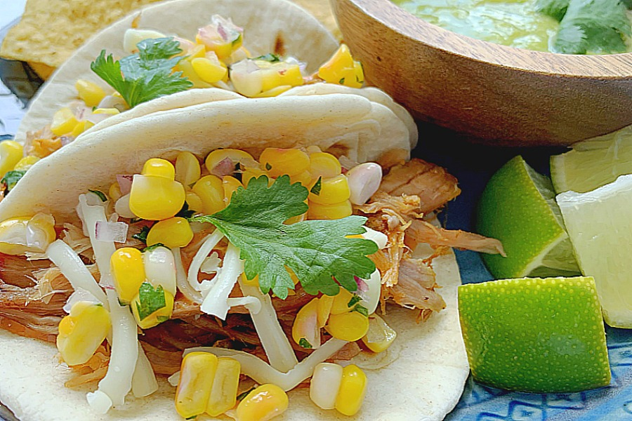 horizontal crop of pulled pork tacos on plate with lime wedges