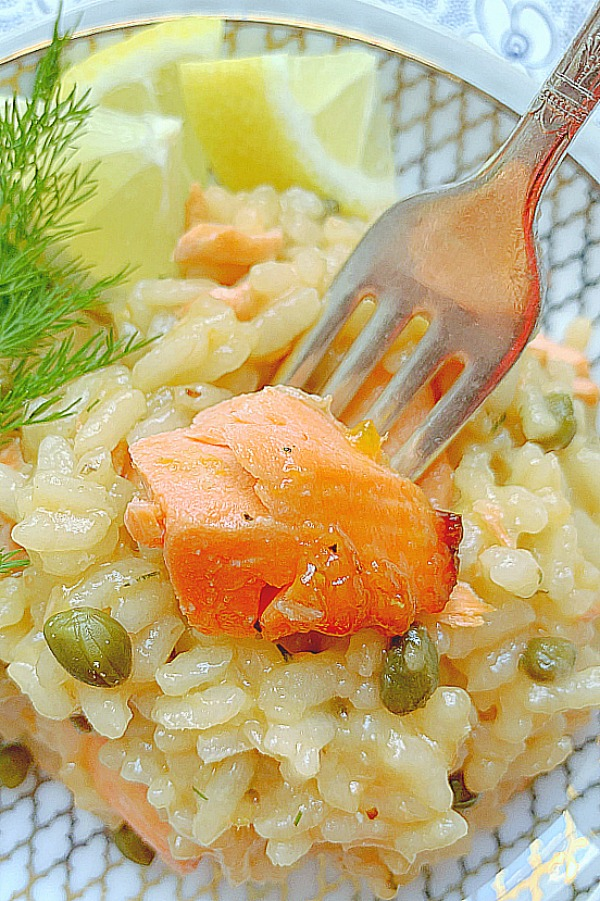 taking a bite of salmon from the salmon risotto