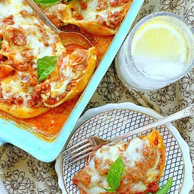 casserole dish and plate full of conchiglioni pasta stuffed shells with meat sauce