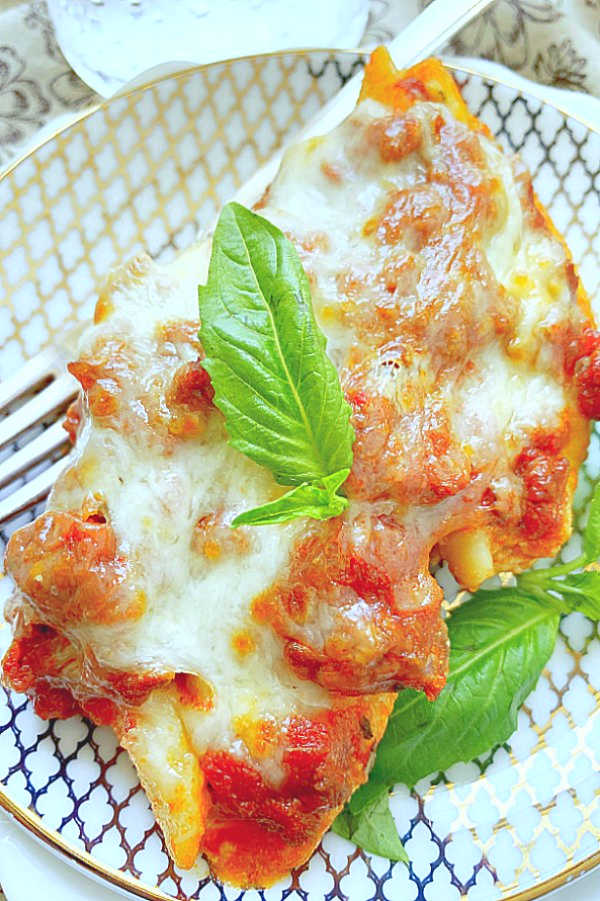 stuffed shells with meat sauce and topped with mozzarella on plate