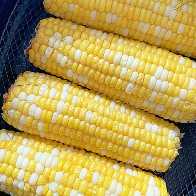 four ears of corn on the cob in the air fryer basket