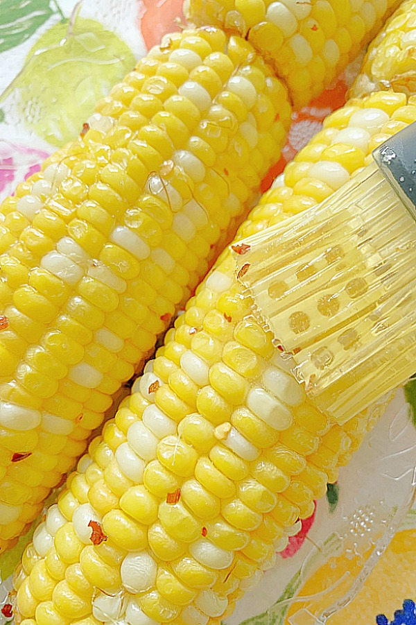 brushing the air fryer corn on the cob with honey butter