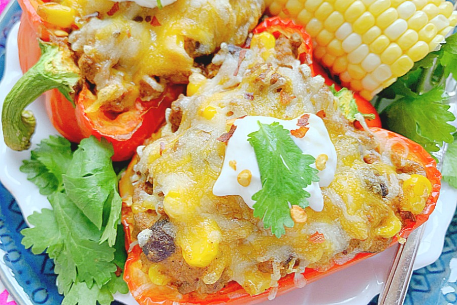 taco stuffed peppers on plate with corn on the cob