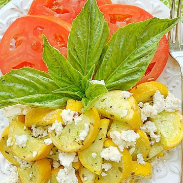 yellow squash topped with feta on a plate with sliced tomatoes and fresh basil