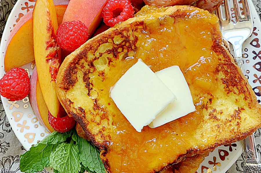 buttermilk french toast topped with peach syrup and butter