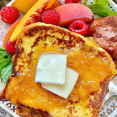buttermilk french toast on a plate with peaches, raspberries and sausage