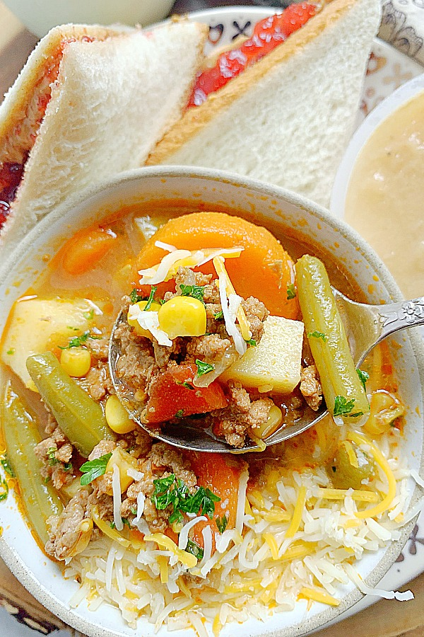 dipping a spoon into a bowl of campfire stew