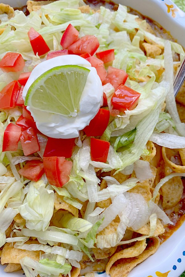 close up view of frito pie topped with lettuce, tomato and sour cream