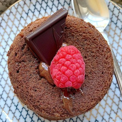overhead shot of lava cake on plate topped with chocolate and a raspberry