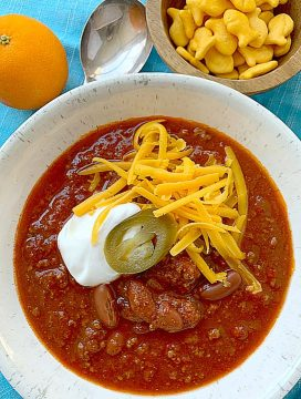 chili in a bowl topped with cheese and sour cream