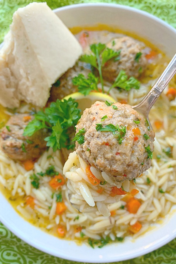 taking a bite of a meatball from easy italian wedding soup