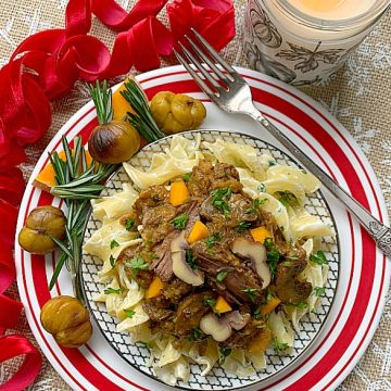 chestnut beef stew on a plate with egg noodles