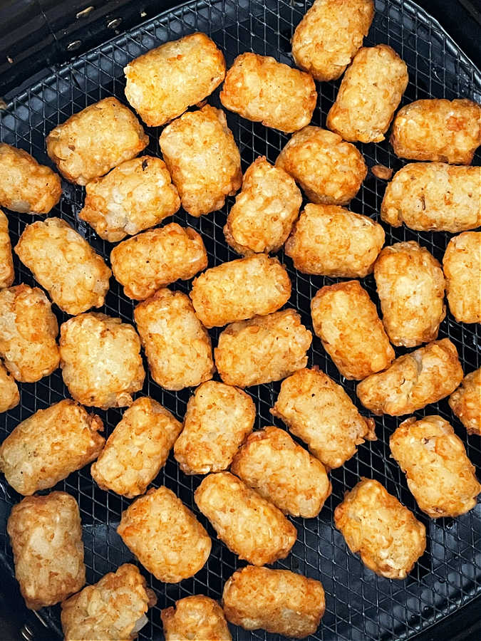tater tots in the basket of an air fryer