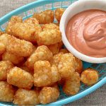 air fryer tater tots in a basket with fry sauce on the side
