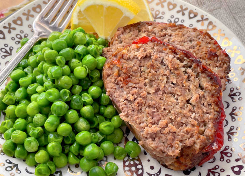 horizontal crop of air fryer meatloaf on a plate with peas