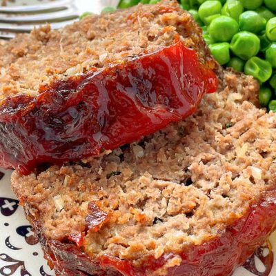 two slices of meatloaf on a plate with peas