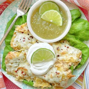green chicken enchiladas on a plate topped with sour cream