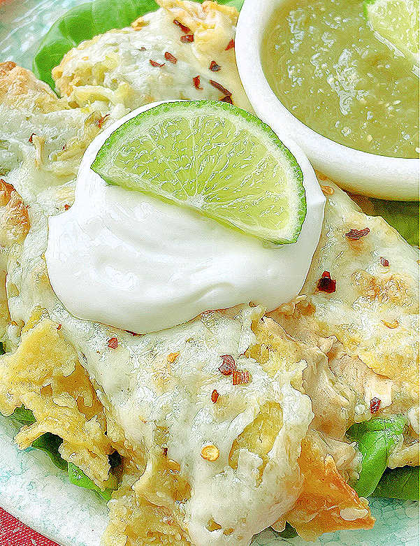 close up photo of green chicken enchiladas topped with sour cream and salsa on the side