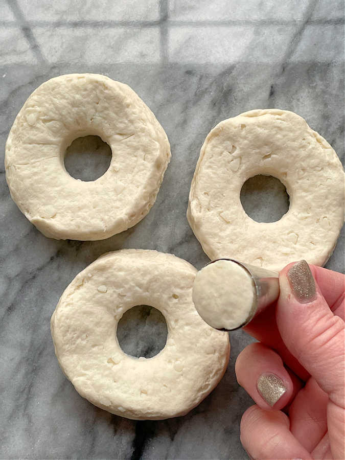 cutting holes in biscuit dough to make donuts