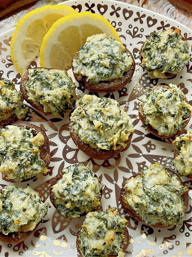air fryer stuffed mushrooms on a plate with lemon slices