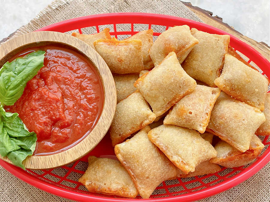 air fryer pizza rolls in a basket with marinara for dipping