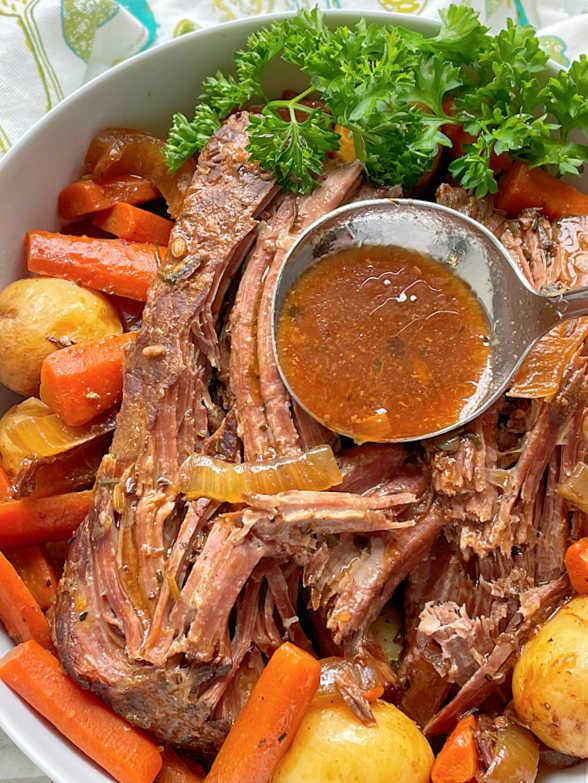 ladling broth over the pot roast