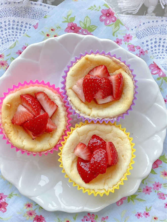 three air fryer cheesecakes on a plate topped with fresh strawberries
