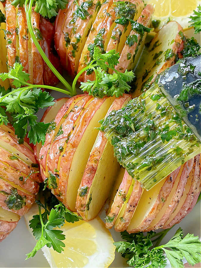brushing parsley butter on air fried hasselback potatoes