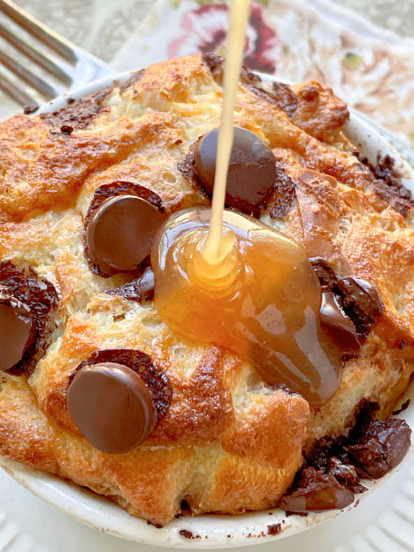 pouring the bourbon butter sauce over the air fryer bread pudding in a ramekin dish