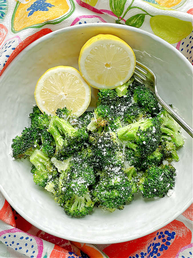air fryer broccoli in a bowl with lemon halves