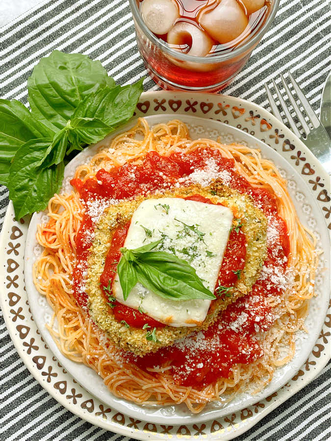 air fryer chicken parmesan on a plate of angel hair pasta