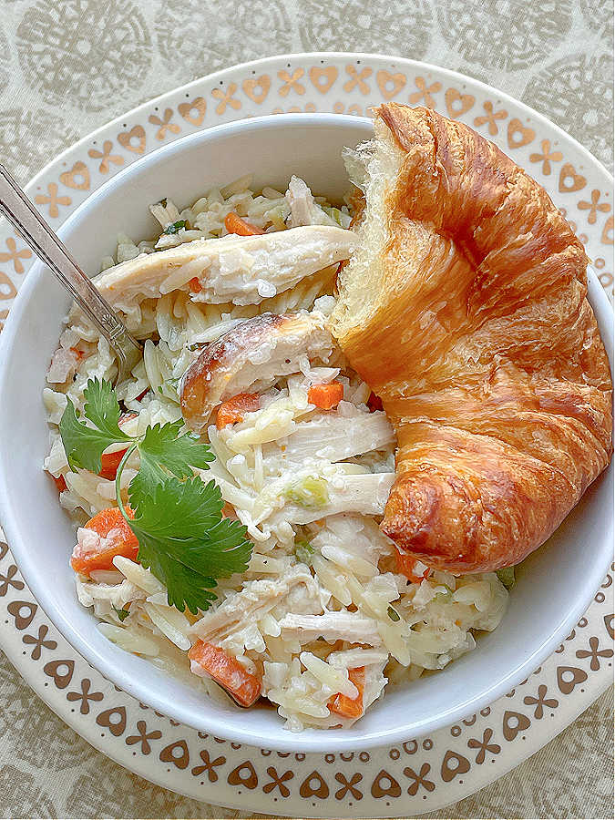 creamy chicken risoni in a bowl with a croissant on the side