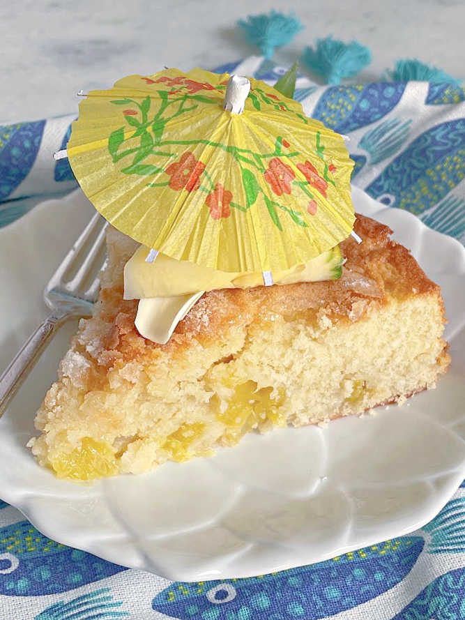 a slice of french pineapple cake topped with a cocktail umbrella
