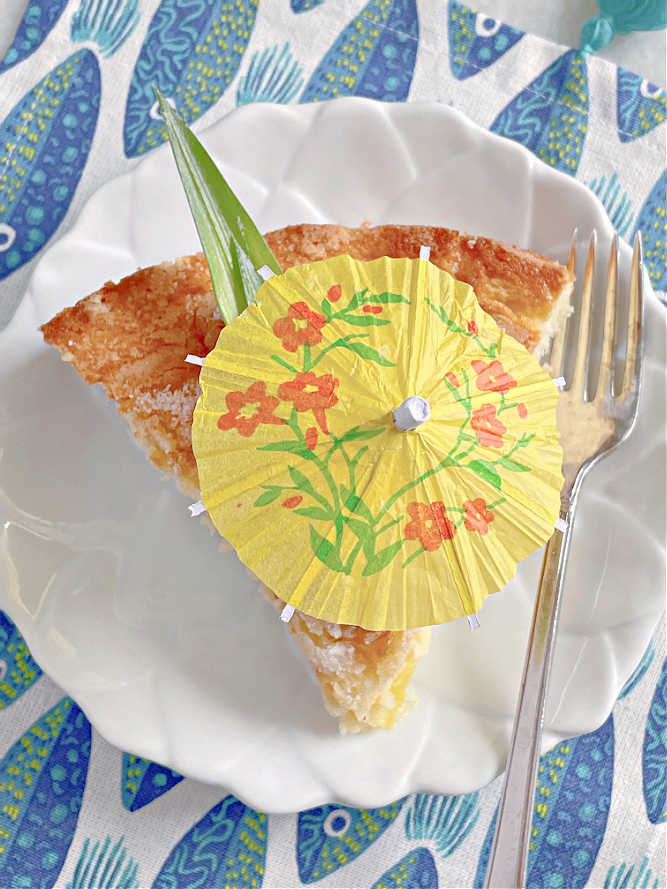 view from the top - a slice of pineapple cake topped with a cocktail umbrella