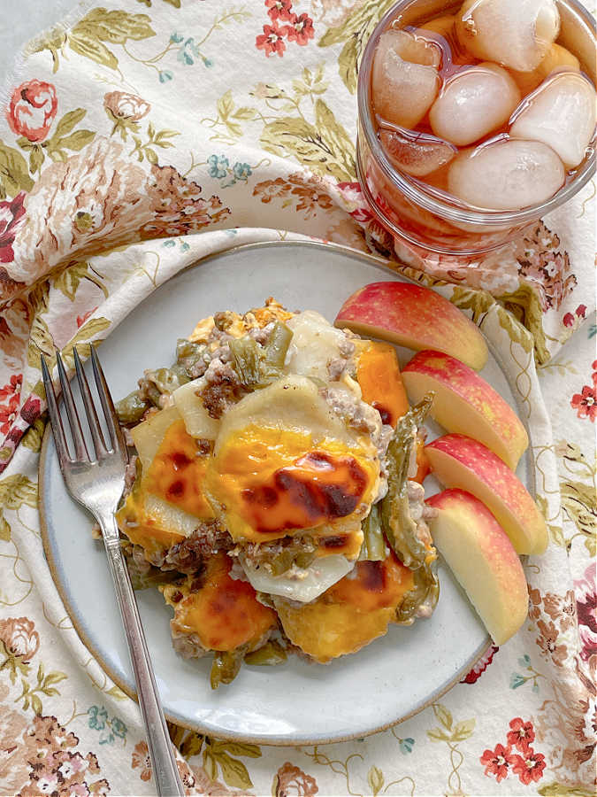 hamburger potato casserole on a plate with apple slices and iced tea