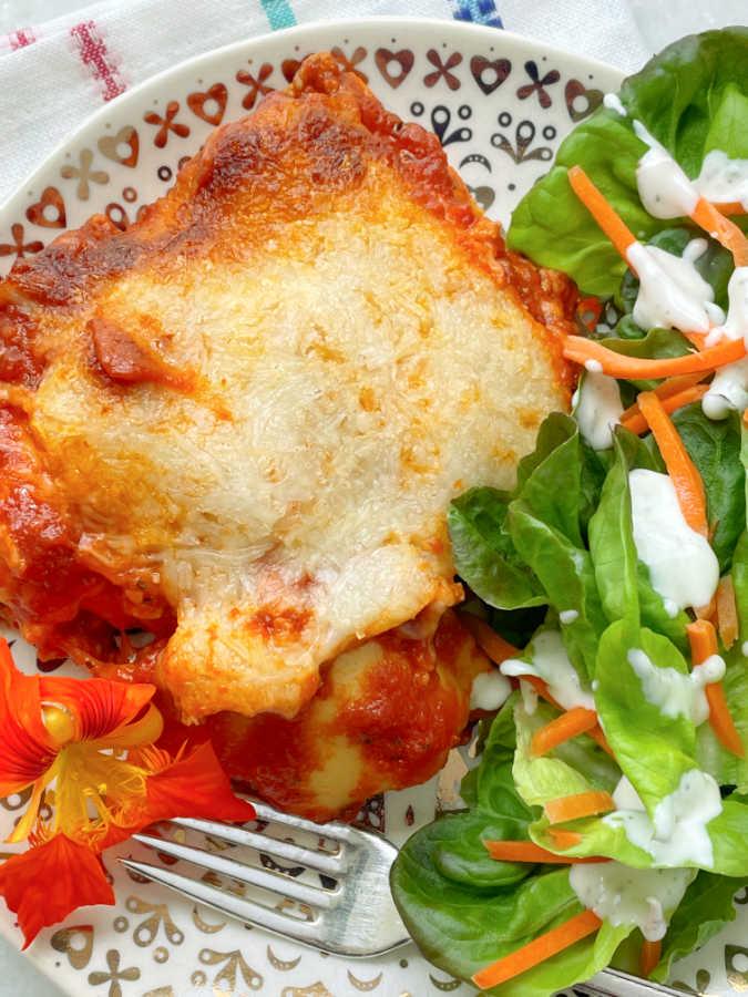 a slice of ravioli lasagna on a plate with tossed salad