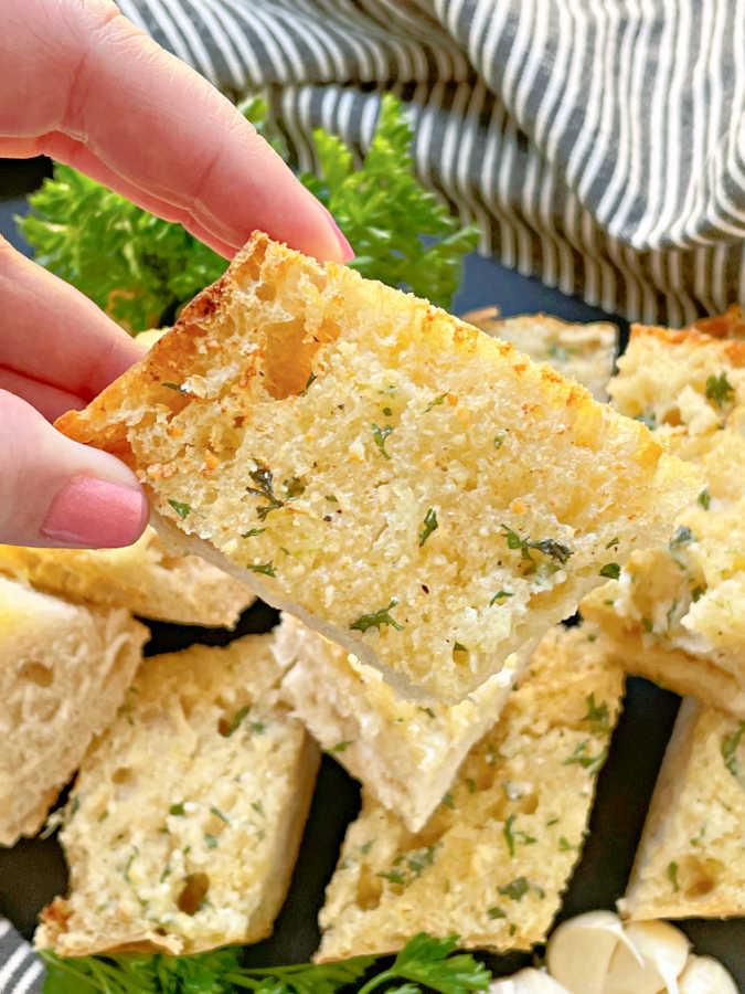 taking a bite of a slice of air fryer garlic bread