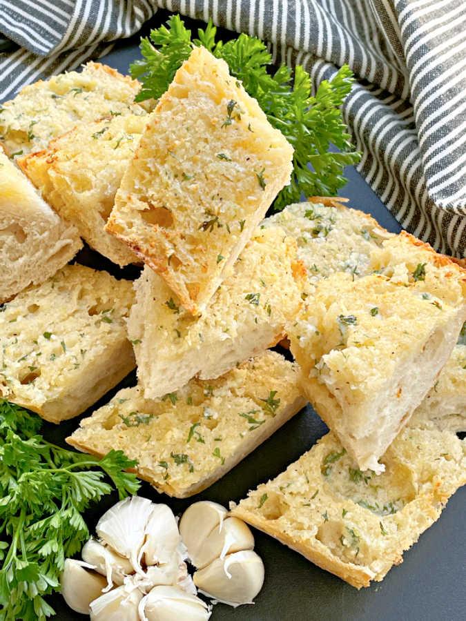 slices of air fryer garlic bread on a cutting board with parsley and garlic garnish