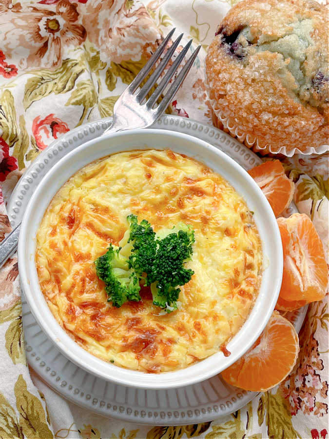 air fryer quiche pictured with orange sections and a blueberry muffin on the side