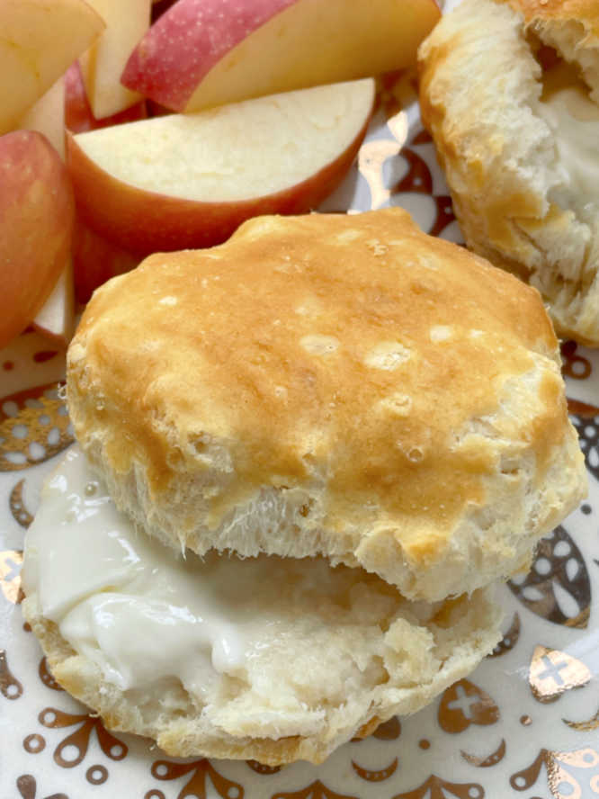 showing a frozen biscuit cooked in the air fryer split and buttered