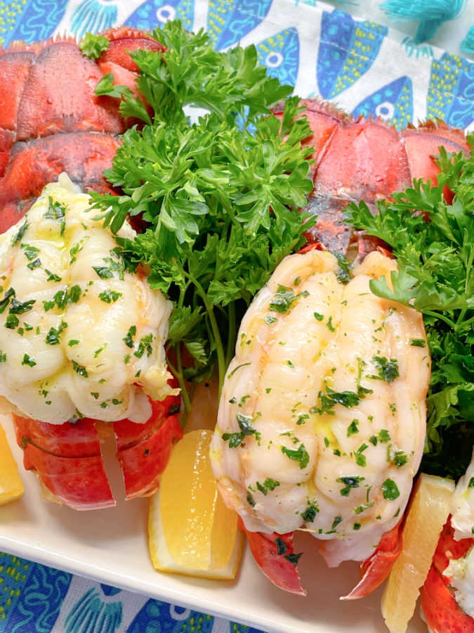 butterflied air fryer lobster tails on a platter with fresh parsley and lemon wedges